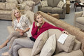 Mother and daughter sitting on sofa while looking at price tag in furniture store Royalty Free Stock Photography