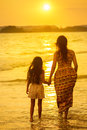 Mother and daughter standing on the beach rear view of a Royalty Free Stock Photos