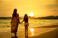 Mother and daughter standing on the beach rear view of a Royalty Free Stock Images