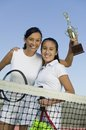 Mother and daughter standing at net on tennis court holding trophy portrait low angle view Stock Photos