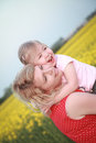 Mother and daughter standing in rapeseed field and smiling beautiful women Stock Images