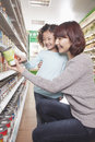 Mother and Daughter in Supermarket Shopping, Kneeling and Looking at a Product Royalty Free Stock Photo