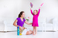 Mother and daughter sweeping the floor young happy her little cute toddler girl cleaning house together in a white sunny Stock Photography