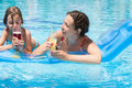 Mother and daughter swimming in pool on an mattress the inflatable with a drink hand Royalty Free Stock Image