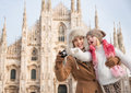 Mother and daughter taking photos in front of duomo milan why not to hang out italian fashion capital on winter holidays with Royalty Free Stock Photo