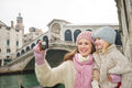 Mother and daughter taking photos in front of ponte di rialto modern family a winter break to enjoy inspirational adventure venice Stock Image