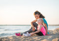 Mother and daughter talking and sitting on the beach Royalty Free Stock Photo