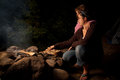 Mother and daughter tending to a campfire at night Royalty Free Stock Images