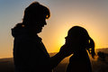 Mother daughter touch silhouetted holding showing affections touching her sunset Royalty Free Stock Photo