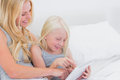 Mother and daughter touching a tablet in bed Royalty Free Stock Photography