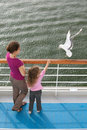 Mother daughter traveling boat feed seagulls Royalty Free Stock Image