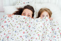 Mother and daughter under the covers look out from Stock Images