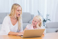 Mother and daughter using laptop in the living room Royalty Free Stock Photos