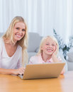 Mother and daughter using laptop in the living room together Royalty Free Stock Photos