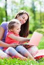 Mother and daughter using laptop outdoors Royalty Free Stock Photo