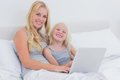 Mother and daughter using a laptop together in bed Royalty Free Stock Image