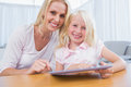 Mother and daughter using tablet pc together in the living room Stock Photography