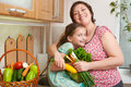Mother and daughter with vegetables and fresh fruits in kitchen interior. Parent and child. Healthy food concept