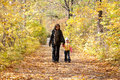 Mother and daughter walk on foot on autumnal park Royalty Free Stock Photo