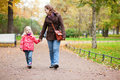 Mother and daughter walking in autumn park Royalty Free Stock Photo