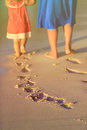 Mother and daughter walking on beach leaving footprint in sand Royalty Free Stock Photo