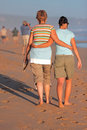 Mother and daughter walking on beach at sunset Stock Image