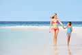 Mother and daughter walking on beautiful beach holding hands Royalty Free Stock Photography
