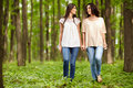 Mother and daughter walking hand in hand through a forest talking Stock Photo