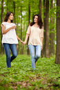Mother and daughter walking hand in hand through a forest talking Royalty Free Stock Photos