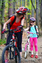 Mother and daughter wearing helmet are cycling on bicycle . Royalty Free Stock Photo