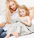 Mother and daughter wiht tablet at sofa family woman baby with computer home on Stock Images