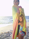 Mother and daughter wrapped in towel on beach smiling portrait of girl Royalty Free Stock Images