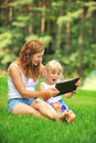Mother and daughter young with her looking at screen of laptop summer day Royalty Free Stock Photos