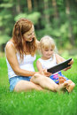 Mother and daughter young with her looking at screen of laptop summer day Royalty Free Stock Images
