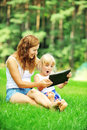 Mother and daughter young with her looking at screen of laptop summer day Stock Image