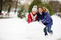 Mother with daughter of younger school age build a snowman in the yard.