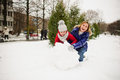 Young woman and girl of school age build a snowman.
