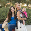 Mother with daughters a happy smiling holds her baby girl in a carrier on her chest while standing in a playground in a park next Stock Photo
