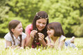 Mother and daughters lying outdoors with flowers Stock Photos