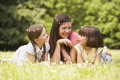 Mother and daughters lying outdoors with flowers Royalty Free Stock Photos