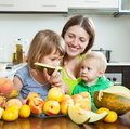 Mother with daughters over table happy together melon and peaches dining at home Royalty Free Stock Photos
