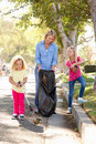 Mother And Daughters Picking Up Litter In Suburban Street Royalty Free Stock Image