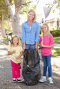 Mother And Daughters Picking Up Litter In Suburban Street Royalty Free Stock Photo