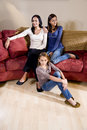 Mother and daughters sitting together at home in l Stock Image