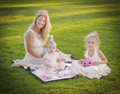 Mother and daughters tea party celebration a her two young all with blond hair blue eyes in their dresses sit on a blanket in the Stock Images
