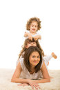 Mother and daughters on top each other her daughter lying fur carpet having fun Royalty Free Stock Photography