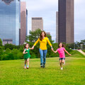 Mother and daughters walking holding hands on city skyline modern over park green lawn Stock Image