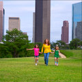 Mother and daughters walking holding hands on city skyline modern over park green lawn Royalty Free Stock Photos