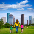 Mother and daughters walking holding hands on city skyline modern over park green lawn Stock Images