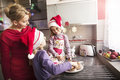 Mother decorating cookies with two little daughters Royalty Free Stock Photo
